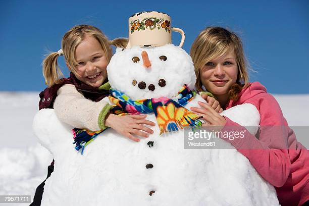 Girls embracing snowman