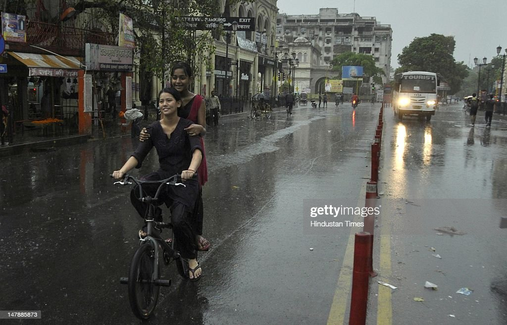 Girls enjoy an early morning bicycle ride through flooded streets after the first rain after dry summer days on July 5 2012 in Lucknow India Heavy...