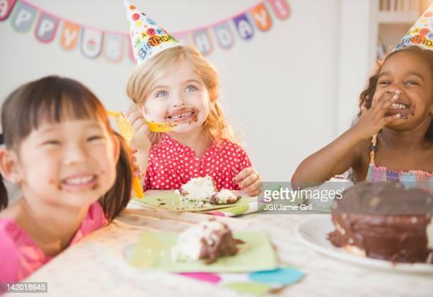 Girls enjoying cake at birthday party
