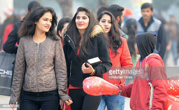 Girls enjoying cold weather at city centre plaza on Christmas on December 25 2014 in Chandigarh India Cold wave conditions continued unabated in...