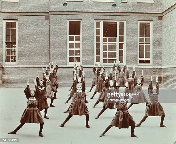 Girls' exercise drill Montem Street School Islington London 1906 A class of girls in the playground lunge sideways with their arms stretching upwards...