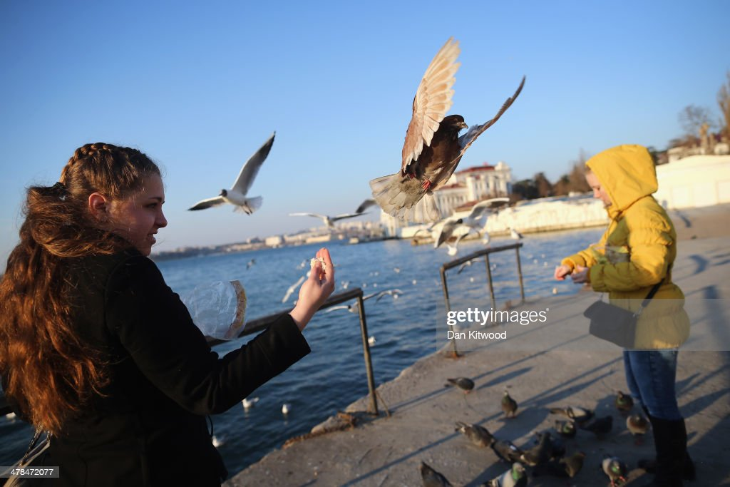 Girls feed pigeons on the harbour wall on March 13, 2014 in Sevastopol, Ukraine. As the standoff between the Russian military and Ukrainian forces continues in Ukraine's Crimean peninsula, world leaders are pushing for a diplomatic solution to the escalating situation. Crimean citizens will vote in a referendum on 16 March on whether to become part of the Russian federation.