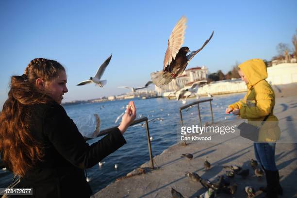 Girls feed pigeons on the harbour wall on March 13 2014 in Sevastopol Ukraine As the standoff between the Russian military and Ukrainian forces...