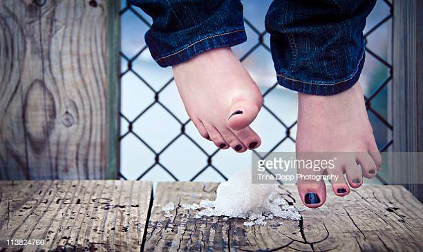 Girls feet dangling over snow on a bench