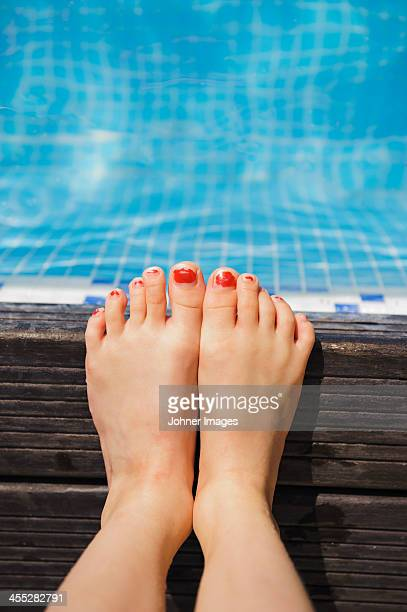 Girls feet on the edge of swimming-pool