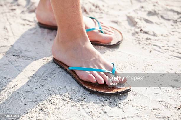 Girl's feet wearing flip-flops at beach