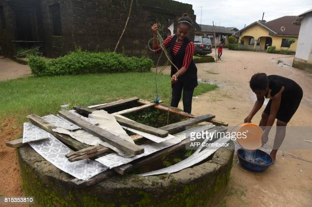 Girls fetch water from a well contaminated by oil pollution at Ogale Town Eleme in southeast Nigeria on June 13 2015 One year after a celebrated...