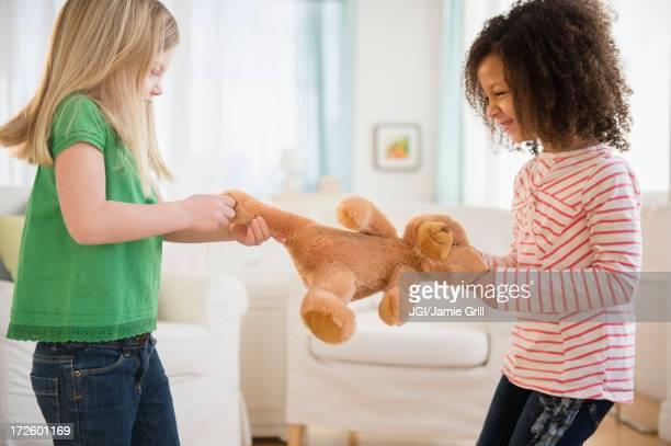 Girls fighting over teddy bear in living room