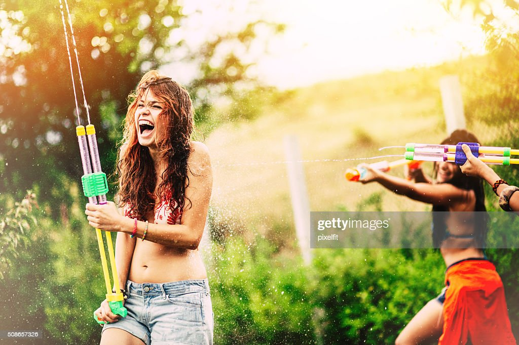 Girls fighting with squirt guns : Stock Photo