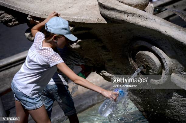 A girls fills her bottle with water off a Barcaccia Fountain in Rome's Piazza di Spagna on July 23 2017 Several areas of Italy including the Po...