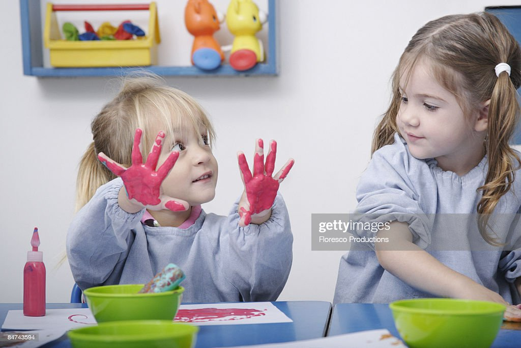 Girls finger-painting in classroom : Stock Photo