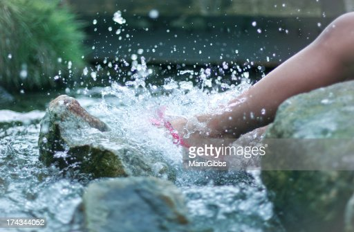 Girl's foot kicking water on the river.