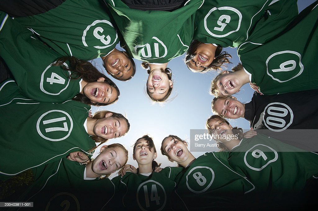 Girls (12-15) football team forming huddle, view from below : Stock Photo