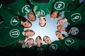 Girls (12-15) football team forming huddle, view from below