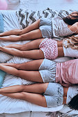 Close up top view of four young women in pajamas lying on the bed