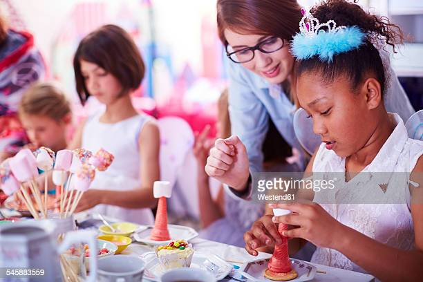 Girls garnishing sweets on a birthday party