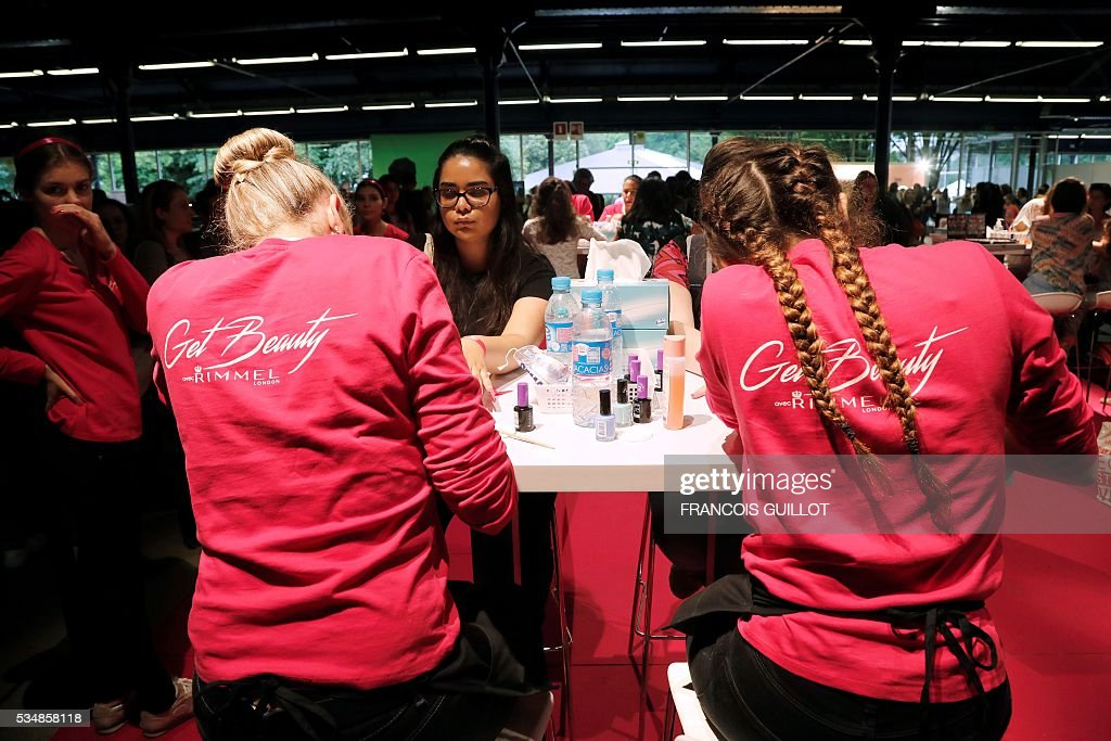Girls get their nails polished during the Get Beauty fair, a beauty and fashion fair inspired by the US 'Beautycon' event gathering of fashion bloggers and YouTube personalities, on May 28, 2016 at the Vincennes' parc floral, eastern Paris. / AFP / FRANCOIS