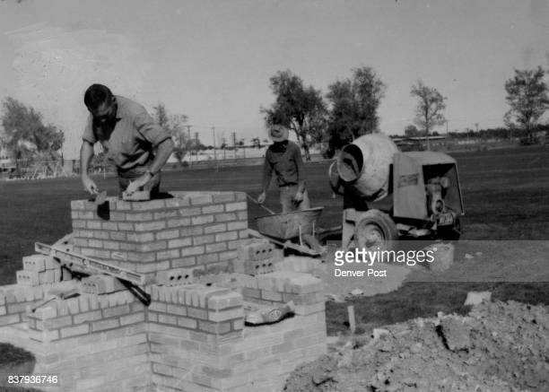 Girls' Gift Going Up Taking shape under the hands of brick contractors Don Lilly and Melvin Crosswhite in Aurora's Del Mar Park is a fireplace...