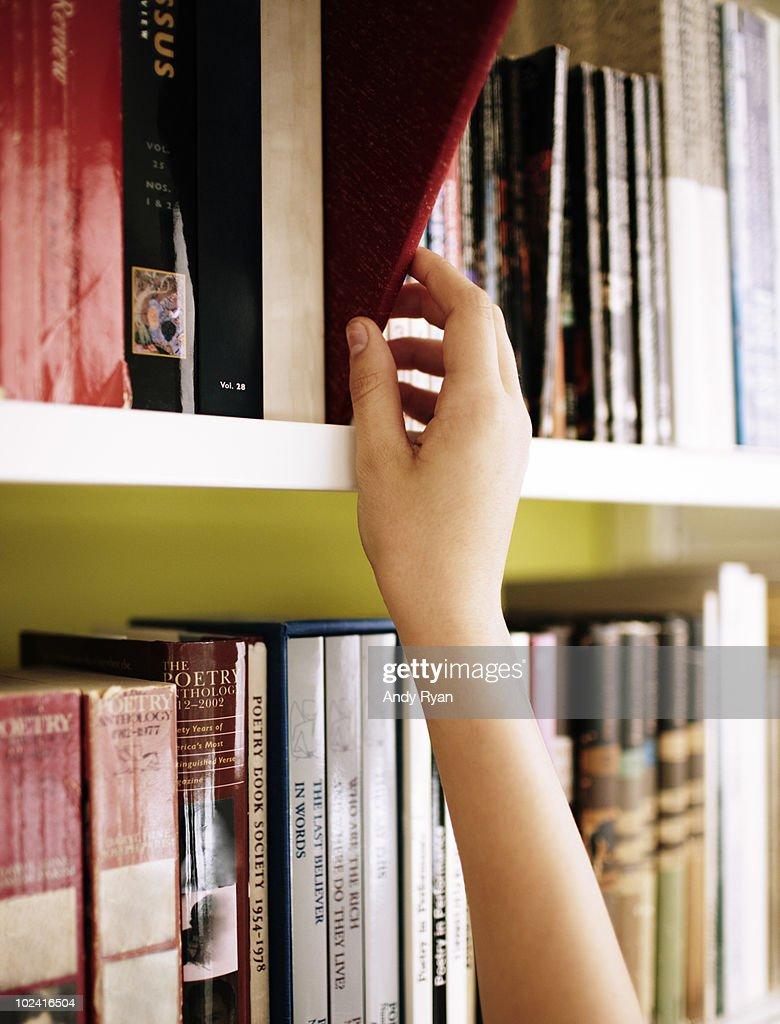 girls hand choosing book from library shelf