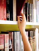 girls hand choosing book from library shelf