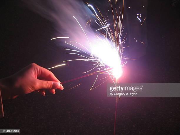 Girl's hand holding sparkler at night