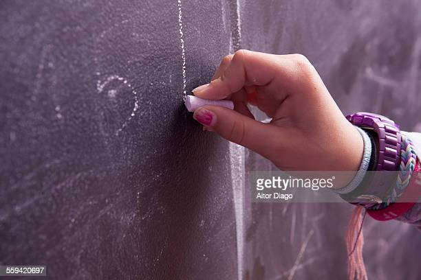 Girl´s hand writing on blackboard.
