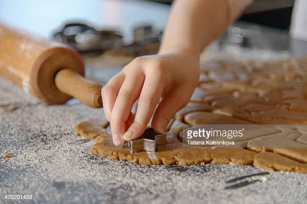 Girls hands cutting Christmas gigerbread cookies.