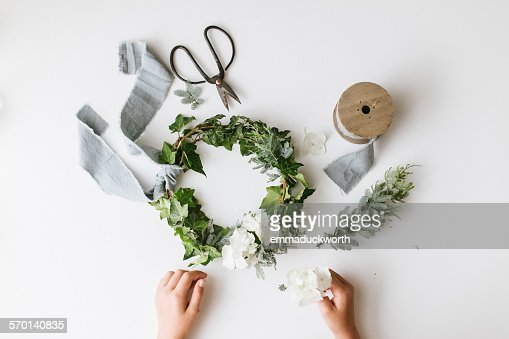 Elevated view of childs hands making a festive christmas foliage wreath