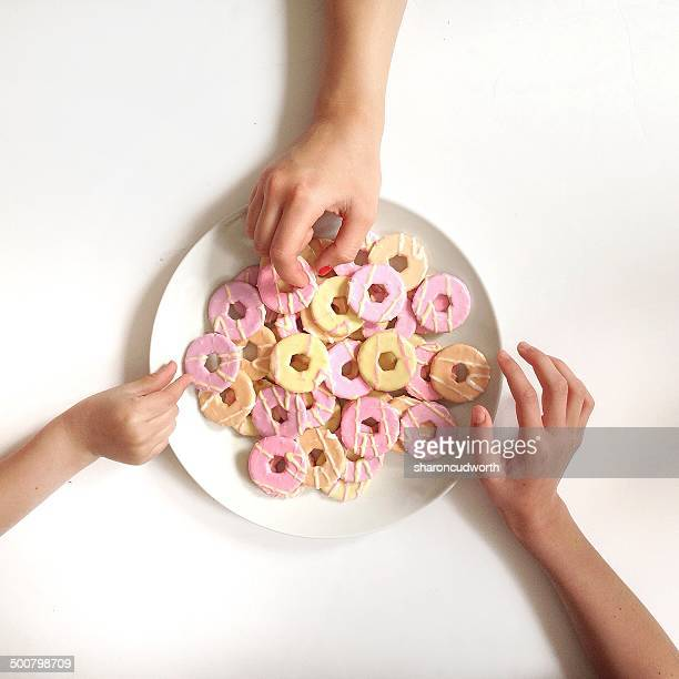 Girl's hands reaching for biscuits from plate