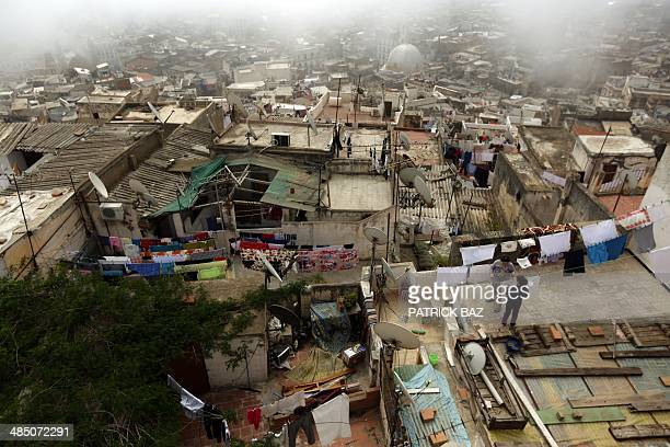 Girls hang laundry as fog covers the old part of Algiers known as the 'Kasbah' on April 16 2014 AFP PHOTO/PATRICK BAZ