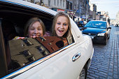 Girls hanging out of limousine window on Royal Mile.