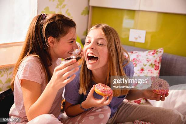 Girls having a fun pyjama party with colourful doughnuts