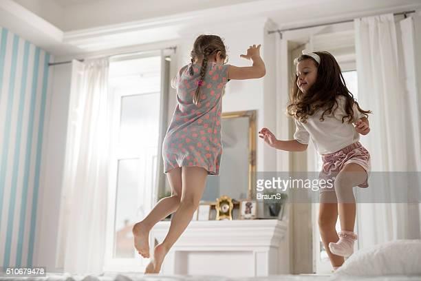 Mädchen Spaß haben im Schlafzimmer und springen auf einem Bett.