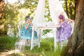 Girls (18-23 months), (2-3) having tea in garden