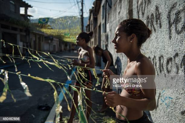 Girls help help to decorate a street for the FIFA World Cup 2014 in Rio de Janeiro Brazil on June 11 on the eve of the opening of the event AFP PHOTO...