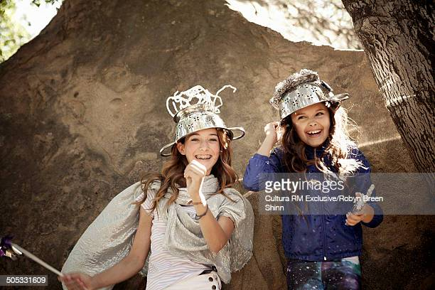 Girls hiding behind rock wearing colander on head