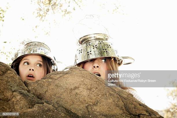 Girls hiding behind rock wearing colander on head
