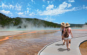Girls wearing hats hiking on vacation. Beautiful Grand Prismatic Spring at Yellowstone National Park.