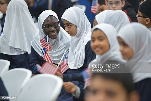 Girls hold US flags while waiting for US President Barack Obama after he spoke at the Islamic Society of Baltimore in Windsor Mill Maryland on...