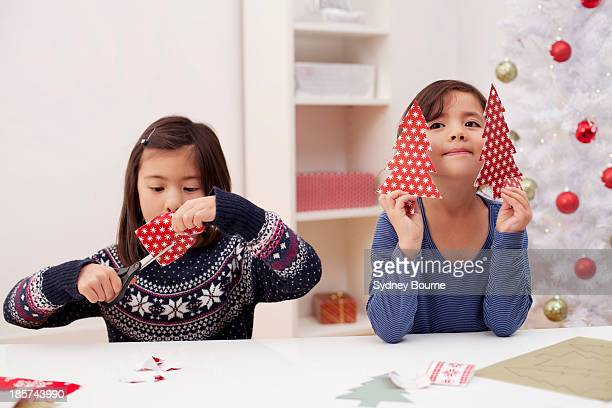 Girls holding and making Christmas decorations