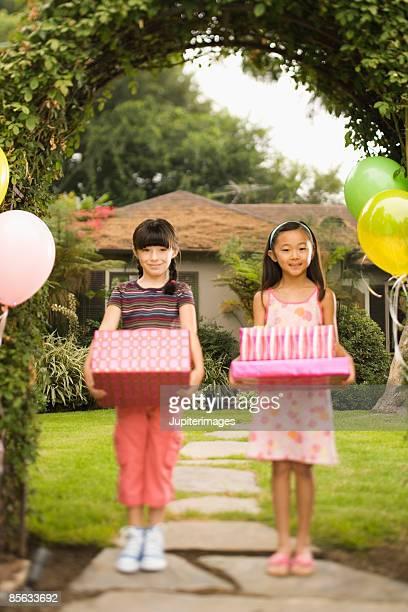 Girls holding birthday presents