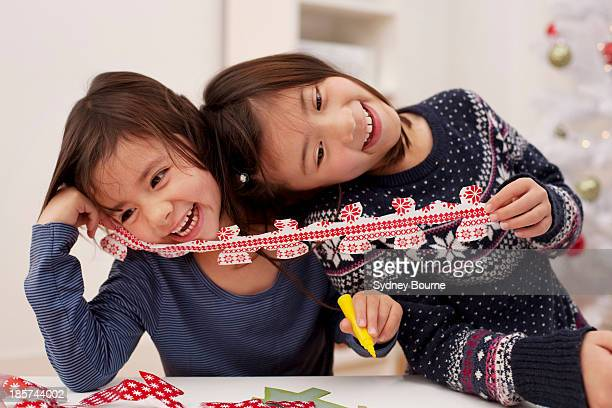 Girls holding Christmas decorations,  laughing