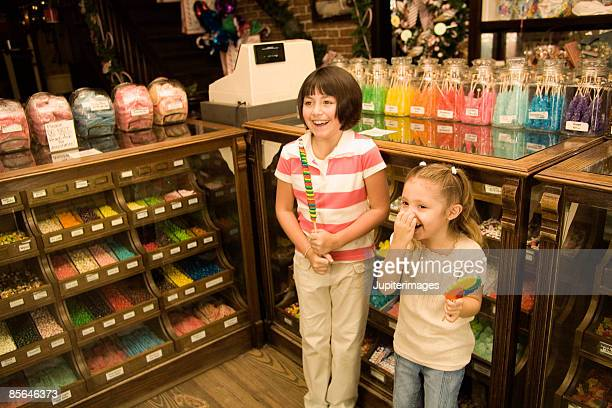Girls holding colorful lollipops in candy shop