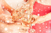 Hands of young girls  holding glasses filled with champagne at new year party