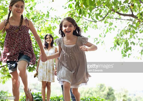 Girls holding hands and running outdoors