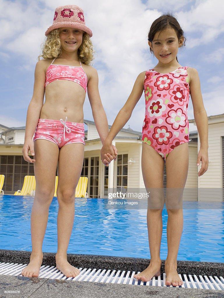 Girls holding hands near pool