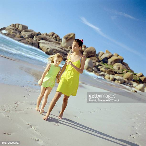 Girls holding hands while walking on beach