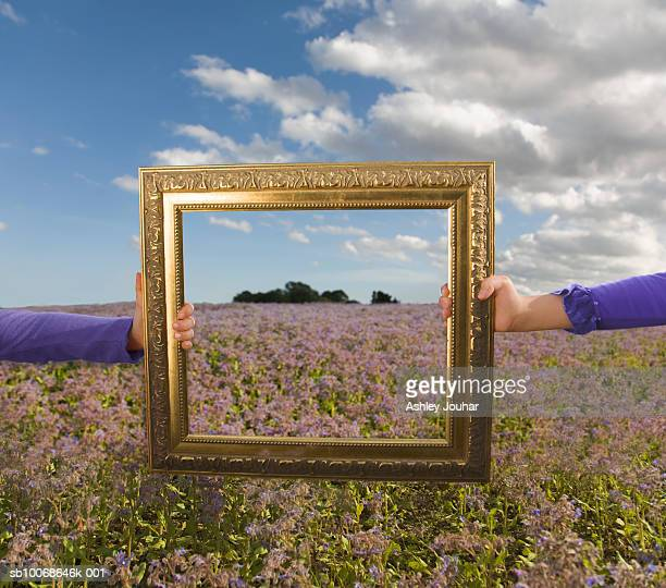 Girls (8-9) holding picture frame in field