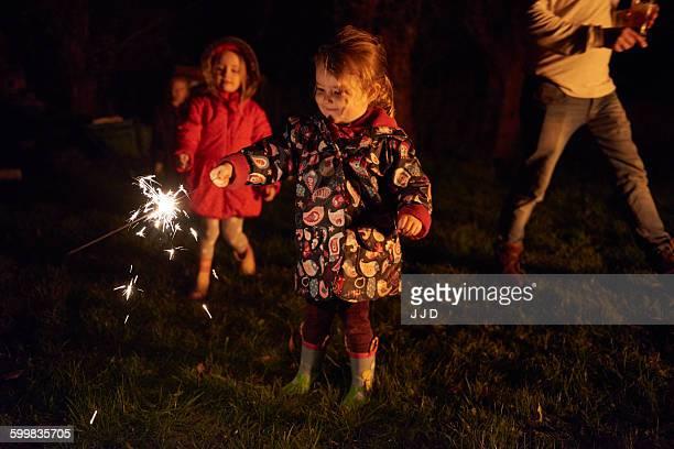 Girls holding sparklers smiling
