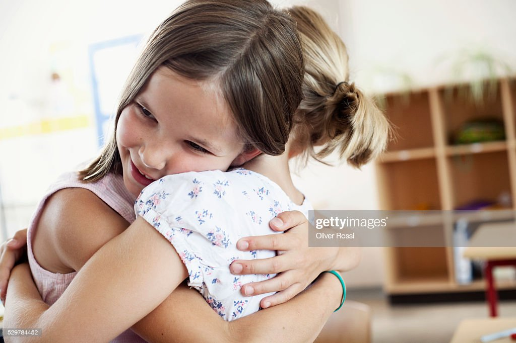 Girls hugging in classroom : Stock Photo